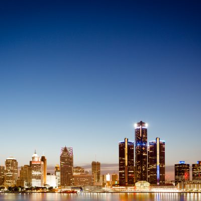 Detroit, Michigan skyline at twilight with the illuminated lights of the waterfront buildings in the CBD reflected in the water of the Detroit River